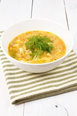 Yellow pea soup in bowl on white wooden background