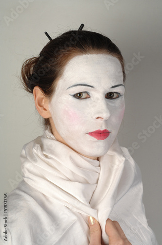 Portrait of a girl in white make-up of a geisha