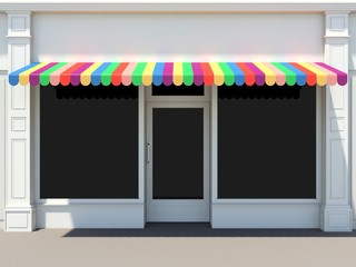 Shopfront in the sun - classic store front with colored awnings