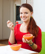girl in red  eats grapefruit with spoon