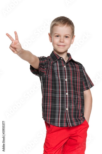 Young boy shows victory sign