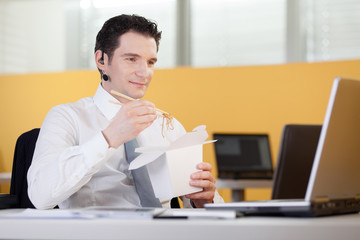 Businessman eating chinese food while having an internet call