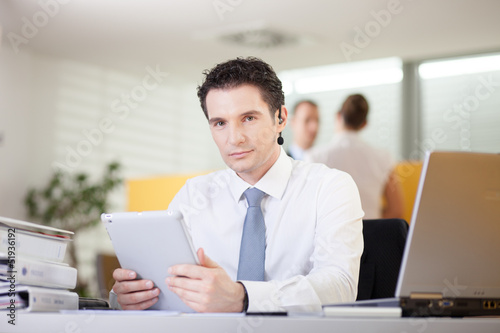 Confident businessman sitting behind the desk