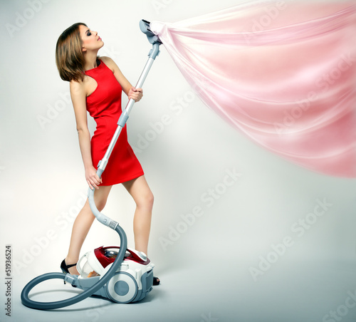 Sexy girl using vacuum cleaner