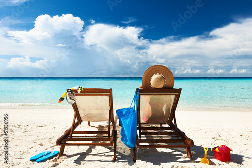 Woman on a tropical beach in chaise lounge
