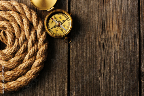 Antique compass and rope over wooden background