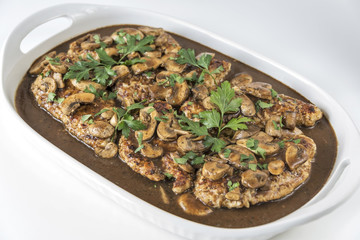 Platter of Chicken Marsala on a white background