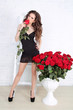 Sexy brunette woman with Red roses at home interior apartment