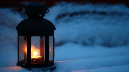 Candle lamp on snowy bench at dusk