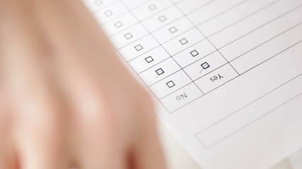 hands filling checklist and answering with no
