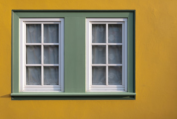 Window on yellow wall of the house.