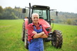 Leinwanddruck Bild - Proud farmer standing in front of his red tractor