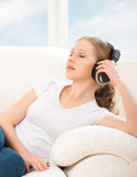 woman in headphones enjoys music while lying on the sofa at home