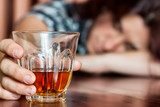 Asleep drunk woman holding an alcoholic drink