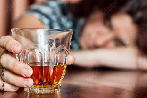 Leinwandbild Motiv Asleep drunk woman holding an alcoholic drink