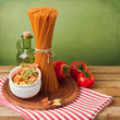 Italian pasta with tomatoes on striped tablecloth