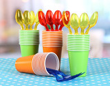 Cups, spoons and forks, of different colors on bright