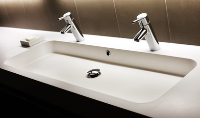 Modern white sink with two shining faucets, tap and soap