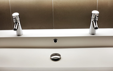 Modern kerrock sink with two shining faucet valves in bathroom