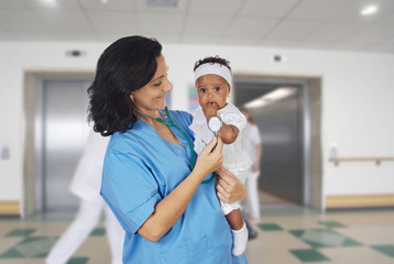 Brunette pediatrician at the hospital with a baby
