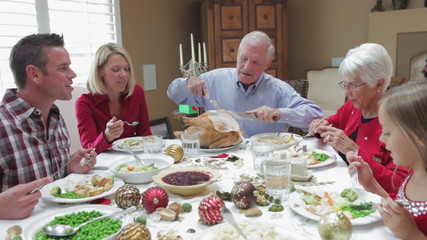 Grandfather Carving Turkey At Family Thanksgiving Meal