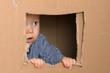 canvas print picture - staunendes Baby schaut vorsichtig aus Fenster
