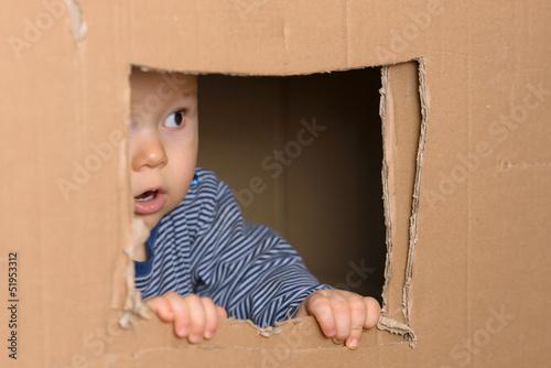 canvas print picture staunendes Baby schaut vorsichtig aus Fenster