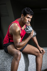 Athletic Indian man exercising with dumbbells