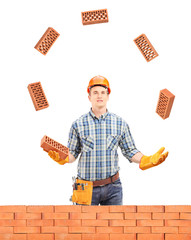 Construction worker juggling with bricks behind a brick wall