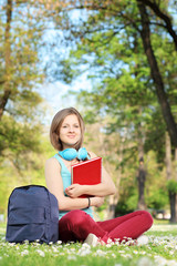 Female student with notebook sitting on a grass in a park