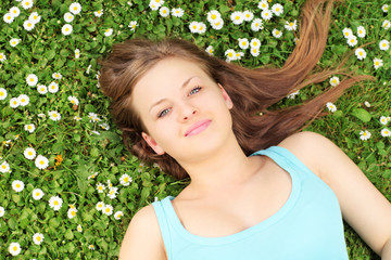 Young beautiful female lying on a green grass with daisies