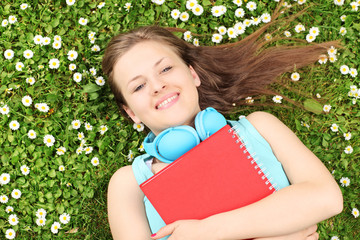 Young female with notebook listening music and lying on a grass