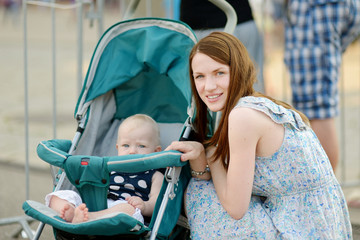 Young mother and her baby in a stroller