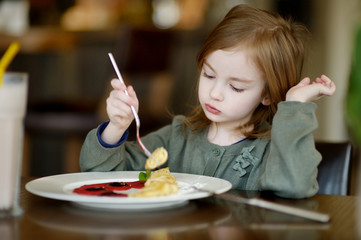 Cute little girl eating pancakes