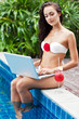 Young woman relaxing near the pool with laptop