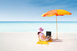 Asian woman typing on laptop under parasol at beach