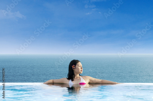 Attractive woman relaxing at infinity swimming pool