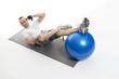Sportlicher junger Mann bei einer Sportübung mit einem Gymnasti
