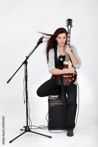 Musician hugging her guitar and posing with her equipment