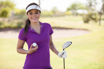 Beautiful young woman holding a golf ball and a club and smiling