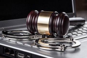 handcuffs and judge gavel on computer concept