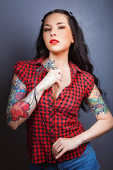 Photo of beautiful girl with tattoos and tattoo machine..