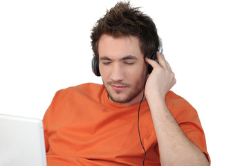 Man listening to his laptop via his headphones