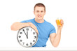 Handsome guy holding a wall clock and glass of orange juice on a