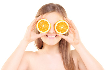 Young pretty female holding an orange half in front of her eyes