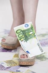 frauen füße mit schuhe und geld