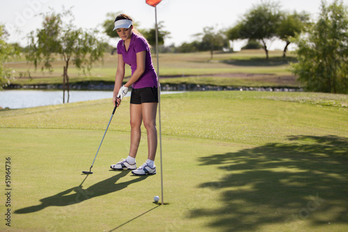 Gorgeous female golfer putting in the green on a sunny day