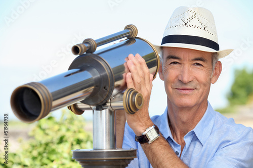 Senior man watching landscape with spyglass