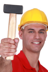 Manual worker proudly showing off hammer