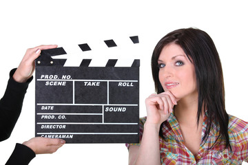 a woman posing near a movie clap